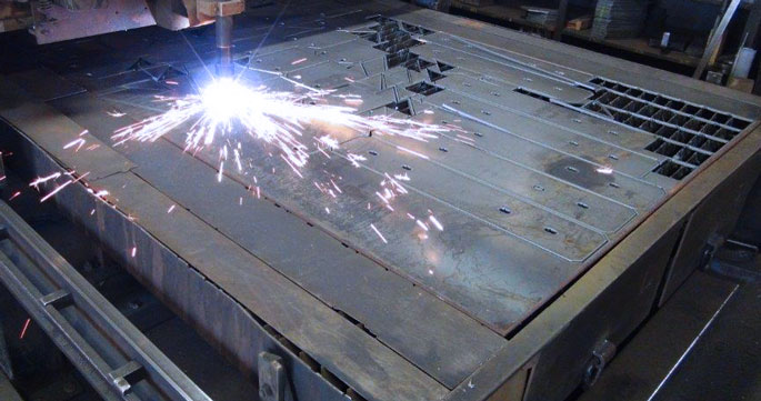 A plasma cutting table cutting steel parts for waste management equipment